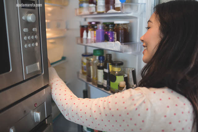 Mulher mexendo na geladeira